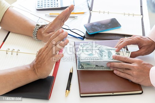848170878istockphoto Business and finance concept, Hand of a businessman refuse money from his partner. 1183281335