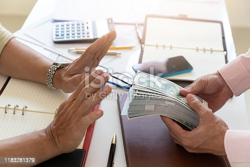 848170878istockphoto Business and finance concept, Hand of a businessman refuse money from his partner. 1183281379