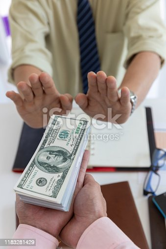 848170878istockphoto Business and finance concept, Hand of a businessman refuse money from his partner. 1183281429