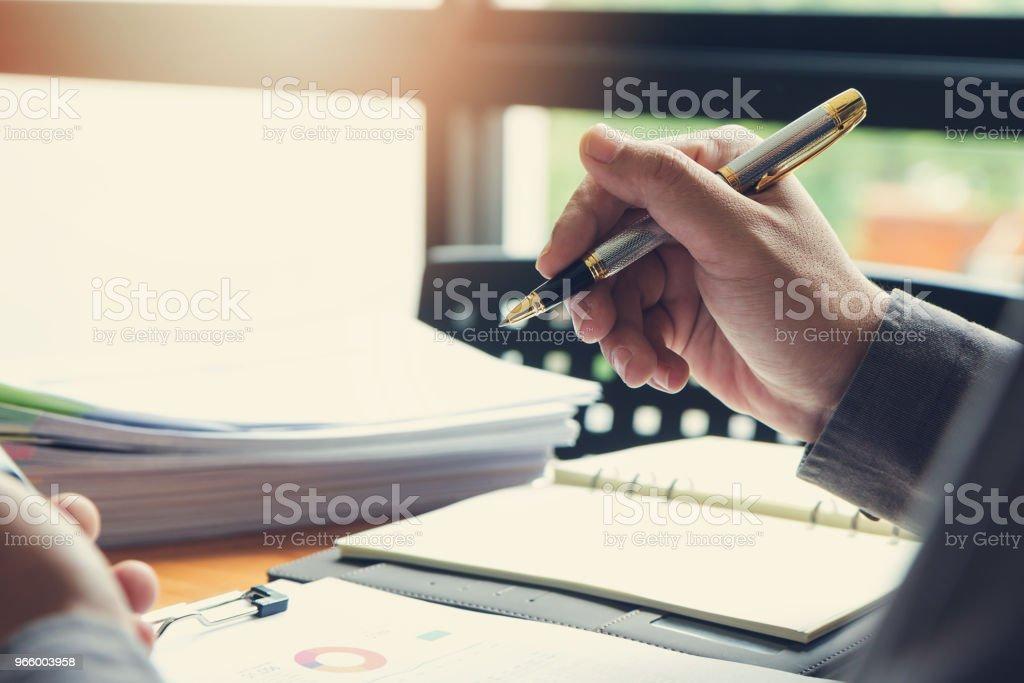 Företag och finans begreppet office arbetar, affärsman håller pennan och diskutera försäljning analys diagram - Royaltyfri Affärsman Bildbanksbilder