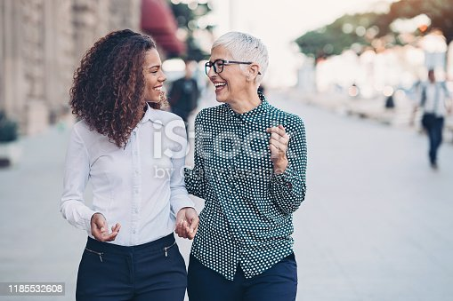 Two businesswomen walking together and talking