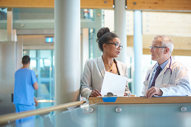 business and medical realtionship. A suited woman and a male doctor wearing a lab coat stand on a stairwell of a modern hospital and discuss some case notes. The woman could be an administrator or business woman . administrator stock pictures, royalty-free photos & images