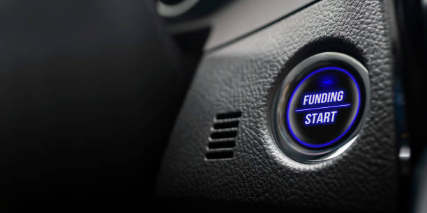 Business and motivation concept. Ignition button with funding start text in real car dashboard. stock photo