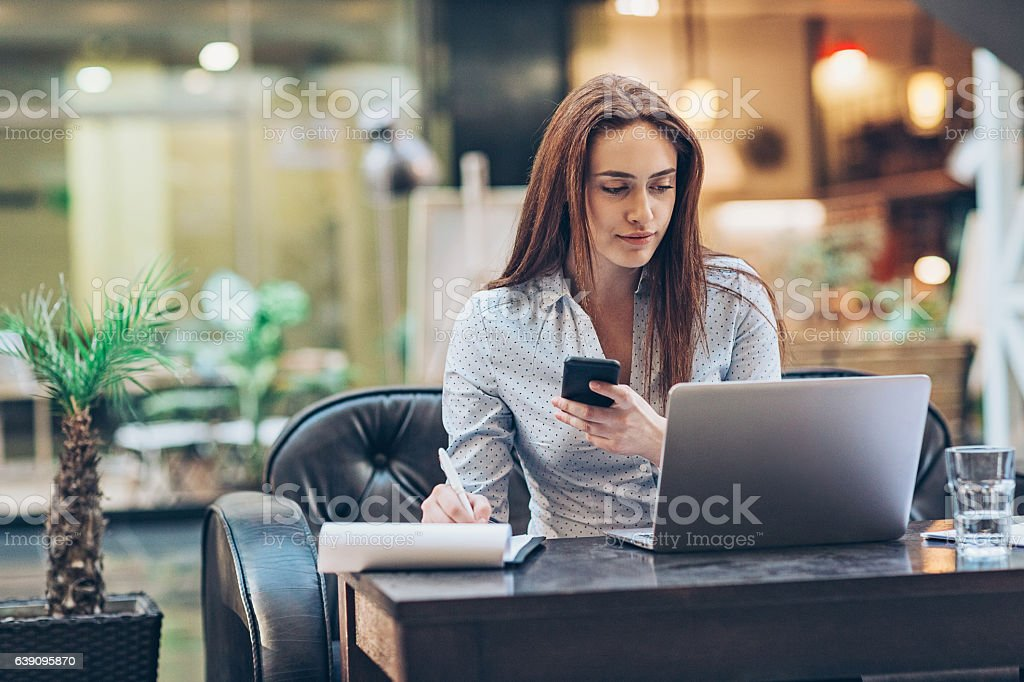 Business and multi-tasking Young businesswoman working in the lobby of a modern business building, with copy space. 30-39 Years Stock Photo