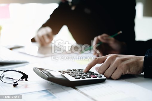 950986656istockphoto Business and partners discussing new plans marketing financial graph data on office table with using calculator in meeting 1136176811