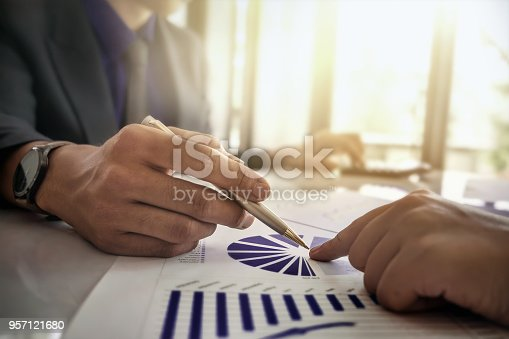 950986656istockphoto Business and partners discussing new plans marketing financial graph data on office table with using calculator in meeting. 957121680