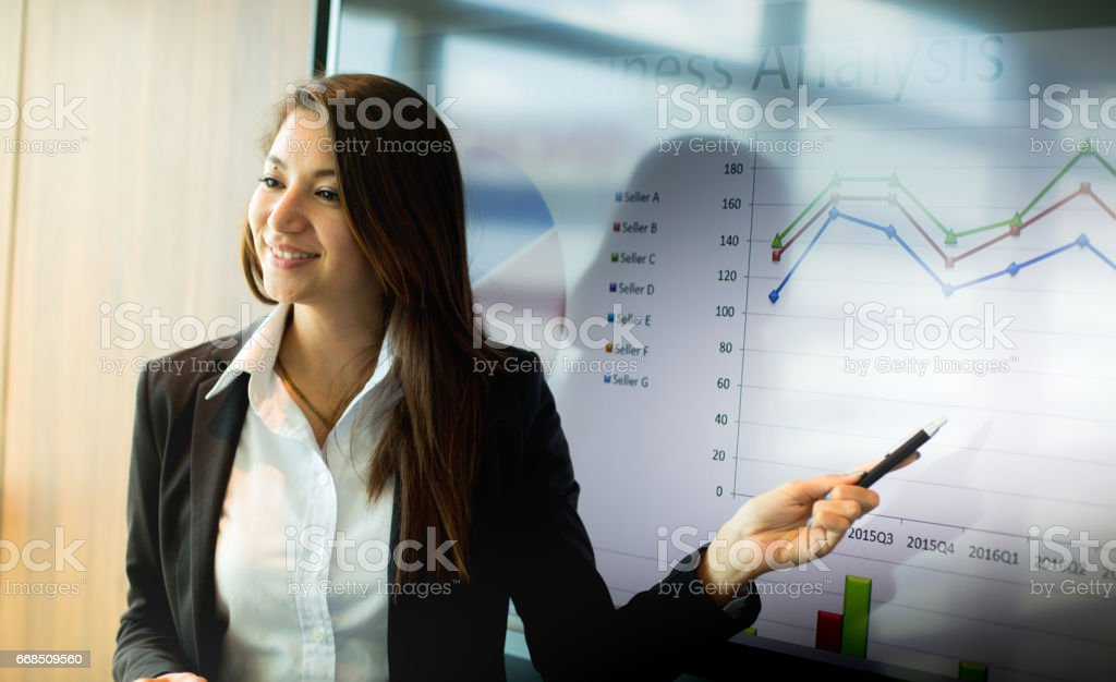 Business and people concept - smiling businesswoman pointing on monitor during presentation in office. stock photo
