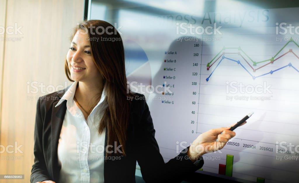 Concepto de negocio y personas - sonriendo a empresaria señalando en pantalla durante la presentación en la oficina. - foto de stock