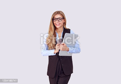 1150572102istockphoto Business and technology. Beautiful happy woman eyeglasses looking at camera and smiling, half turn. Holding  laptop in one hand and phone in other isolated light purple background. 1204185741