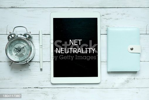 Business and technology concept. Top view of clock,pen,notebook and tablet written with Net Neutrality on white wooden background.