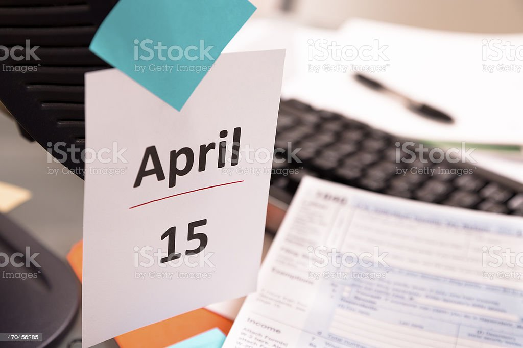 Business: April 15 deadline note. Income tax form on desk. stock photo