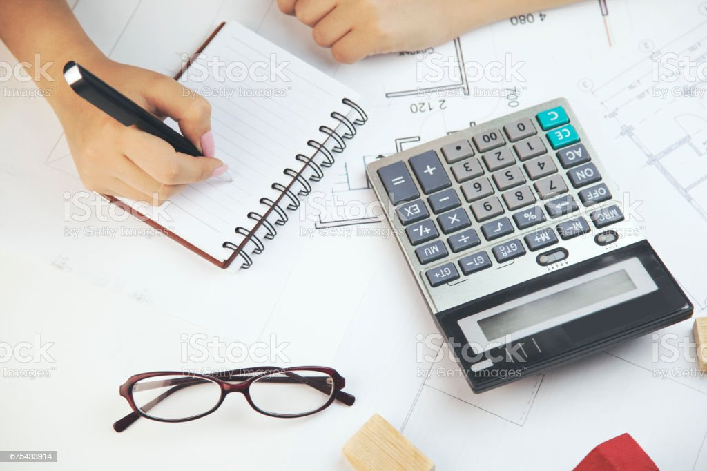 business, architecture, building, construction and people concept - close up of architect hand with blueprint counting on calculator stock photo
