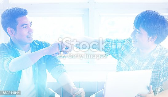 Blurred image, Business people giving fist bump to greeting business successful teamwork, young businessman with Hands together