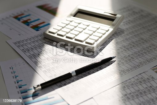 490632340 istock photo Business balance. Black pen and white calculator on against the background of graphs in the sun. 1226638179