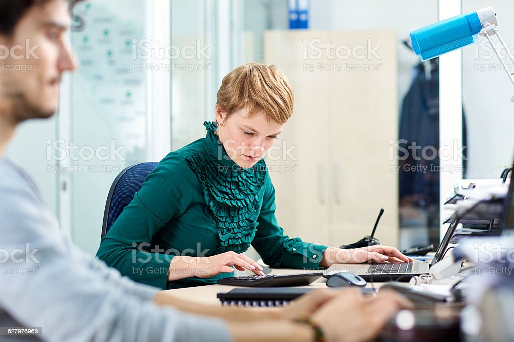 Business blonde woman working at a desk in an office stock photo