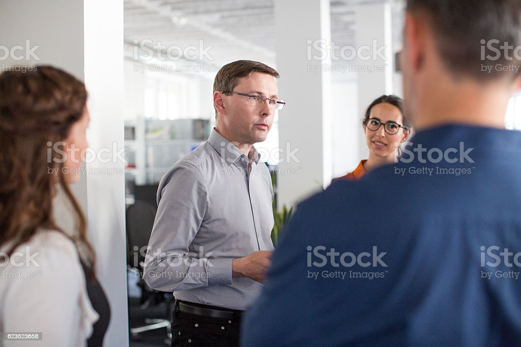 Business boss talking to his colleagues stock photo