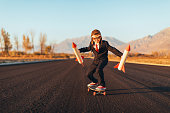 A young business boy dressed in a business suit, aviator cap, and goggles, holds rockets while standing on a skateboard. He is ready to launch his startup business the way forward. This entrepreneur is eager to make money with his new ideas. Image taken in Utah, USA.