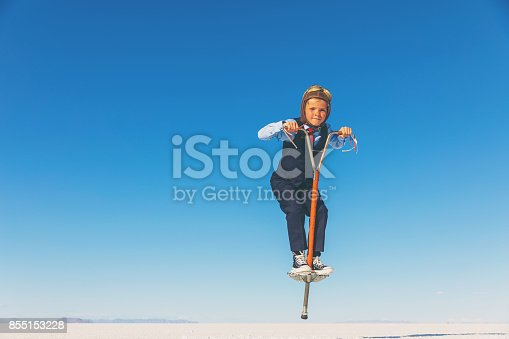A young business boy dressed in business attire, flying goggles and flight cap stands with his pogo stick, ready to bring bounce and sales back to his business. He is jumping on a pogo stick on the Bonneville Salt Flats, in Utah, USA. He is flying high and ready to work for his success.