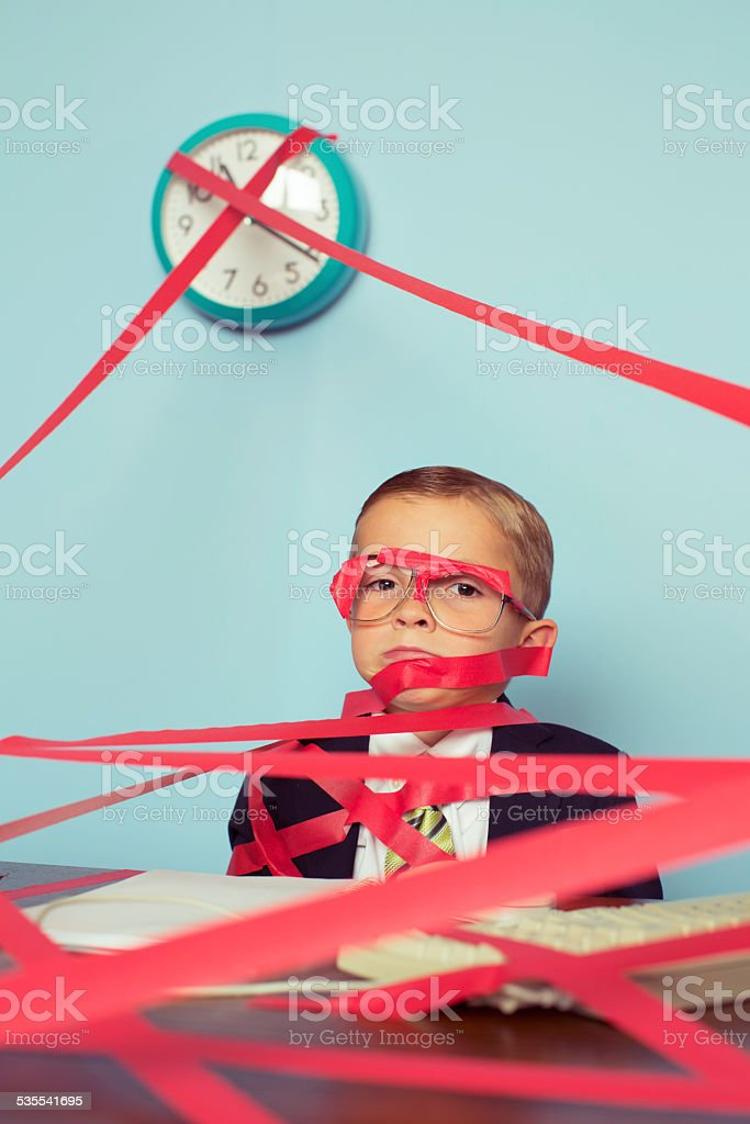 Business Boy Tied Up in Red Tape stock photo