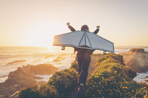 A young boy dressed in business suit and tie wears a homemade jetpack and flying goggles raises his arms in the afternoon sun while running to take off into the air on an outcropping above the surf in Montana de Oro State Park, California. This young entrepreneur is ready to take his new business to new heights.