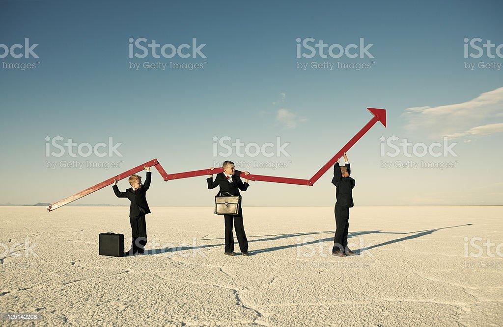 Business Boys Holding Line Graph in Desert stock photo