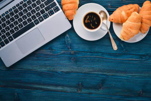 Pequeno almoço de negócios, café e croissants, numa superfície de madeira. Vista superior. Espaço livre para texto. - foto de acervo