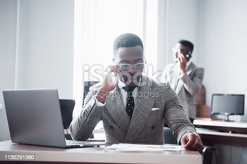 istock Business call. Young african-american businessman in white has mobile phone talk in modern white office interior 1135291380