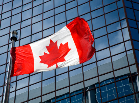 canadian flag in front of modern building