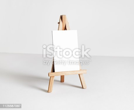 Blank business card on wood holder at white paper background. Responsive design template.
