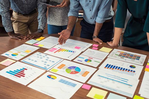 business-casual-team arbeiten an grafiken - geschäftsstrategie stock-fotos und bilder