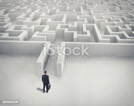 istock Business challenge. A businessman navigating through a maze. Top view 853969296