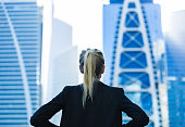 A successful ambitous blonde businessperson standing in dubai city wearing a suit and hands on her waist. Goals and real estate project planning.
