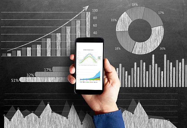 Business chart on blackboard with smart phone in human hand Businessman's hand holding smart phone with a diagram of business strategy drawn on blackboard that represents the concepts of business growth. bull market stock pictures, royalty-free photos & images