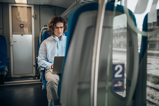 Young businessman traveling with train, using laptop, typing and drinking coffee
