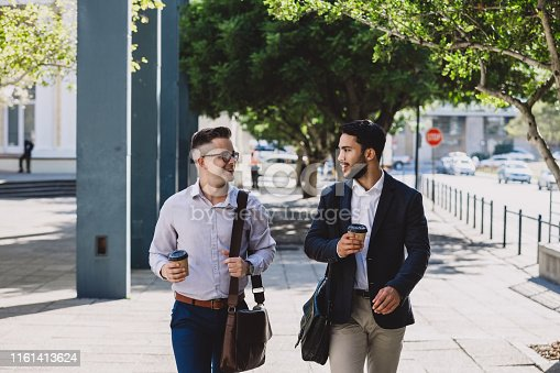 Shot of two young businessmen having coffee and chatting while walking though the city