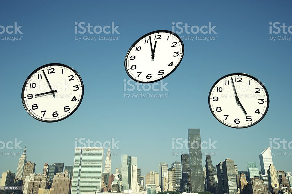 Business Clocks Flying in Sky Above City Skyline stock photo