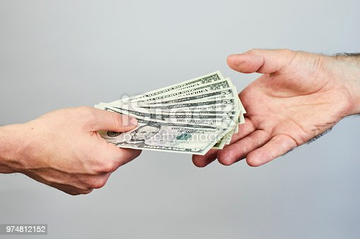 istock Business closeup of two hands exchanging dollars on grey background. 974812152