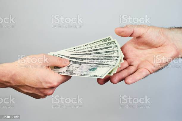 Business closeup of two hands exchanging dollars on grey background picture id974812152?b=1&k=6&m=974812152&s=612x612&h=emoeulsbnj68w3zcc3uk0h2g d66u6vd5mpug3curwc=