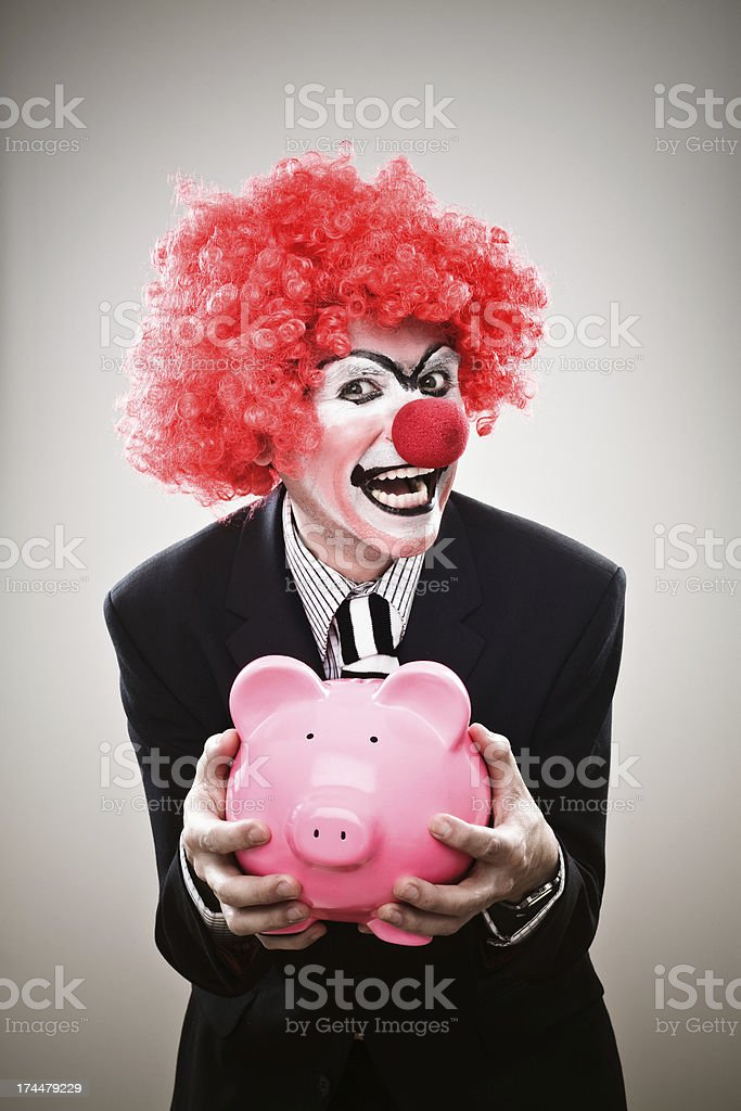 A businessman dressed up as clown holding a pink piggy bank and...