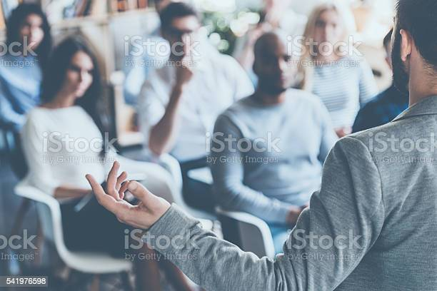 Rear view of man gesturing with hand while standing against defocused group of people sitting at the chairs in front of him