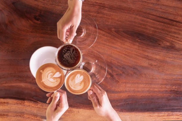 Business coffee break after success discussion cheers the cup of coffee.Friendship meeting in weekend at coffee shop.People hand holding coffee cup and cheers for agreement after negotiation. stock photo