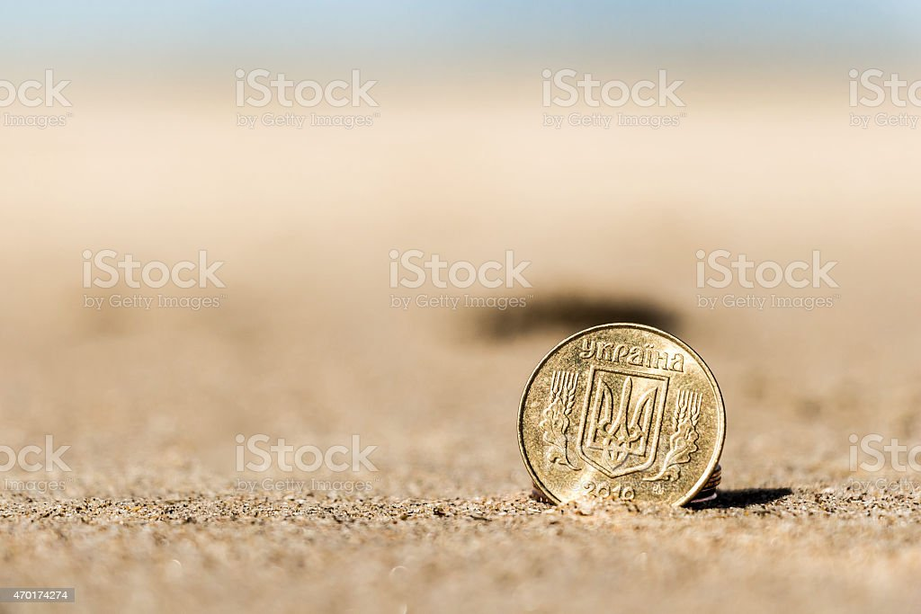 Business coins at holiday in the beach sand stock photo