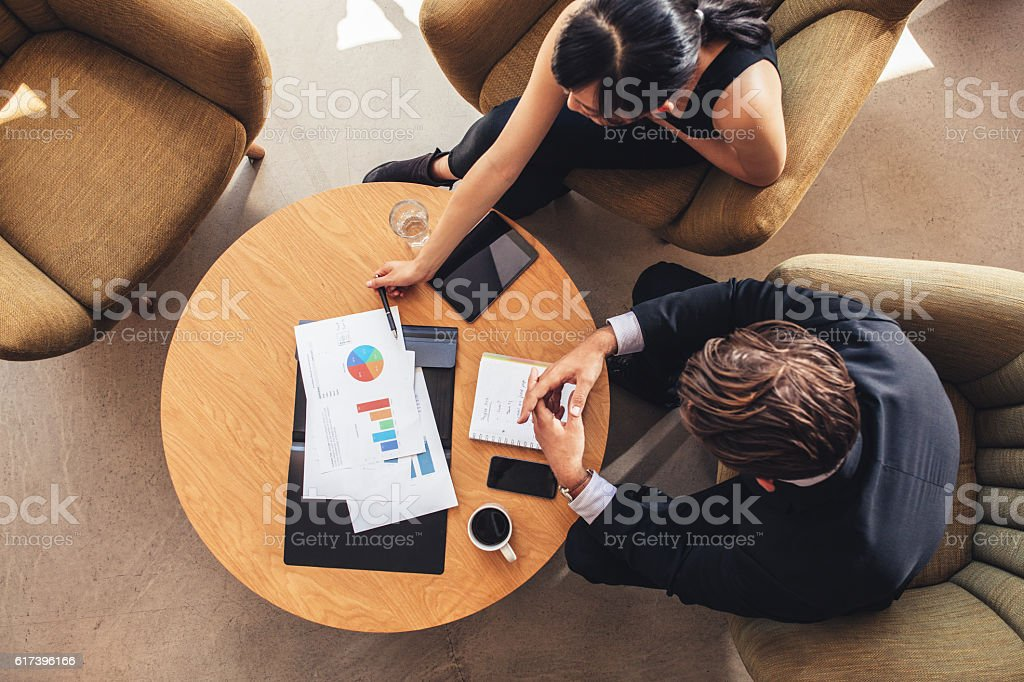 Business colleague sitting at table with charts stock photo