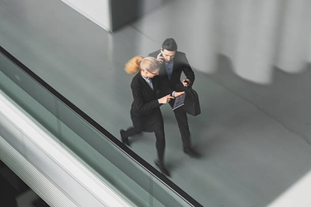 Business Colleague Talking As They Walk Through Office Lobby – Foto