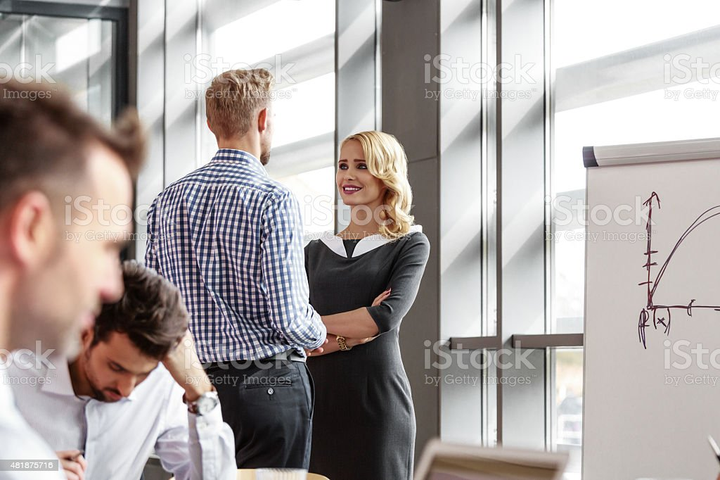 Business colleague talking in an office An attractive businesswoman wearing grey dress talking with his business colleague in an office. On the foreground two defocused businessmen working. 2015 Stock Photo