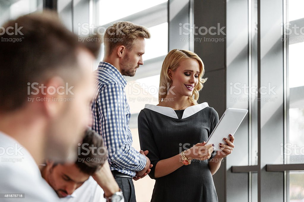Business colleague talking in an office An attractive businesswoman wearing grey dress talking with his business colleague in an office, holding a digital tablet in hands. On the foreground two defocused businessmen working. 2015 Stock Photo