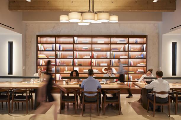 混雑しているデスクでビジネス部門の同僚オープン プラン オフィス - 図書館 ストックフォトと画像