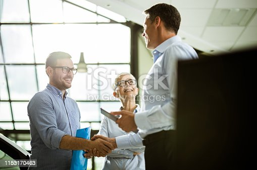 Happy businessman shaking hands with car salesperson while being in a showroom with his female colleague. Focus is on young man and senior woman.