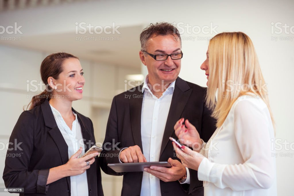 Business colleagues chatting in office building lobby stock photo