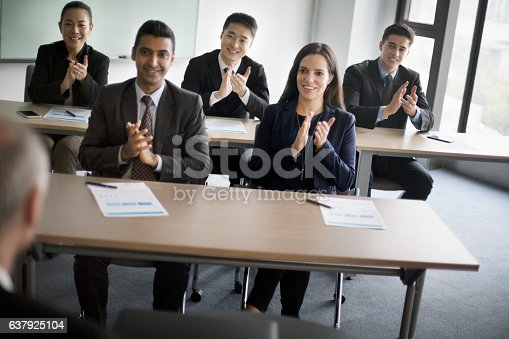 637940820 istock photo Business colleagues clapping hands in learning seminar office classroom 637925104